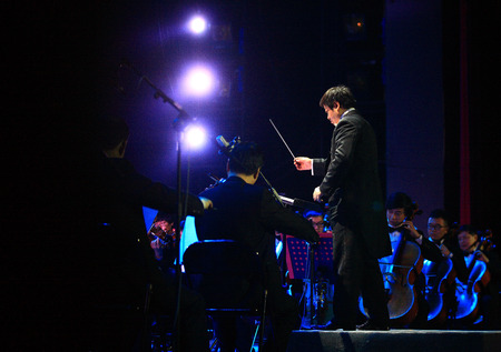conducting: Conductor conducting on stage