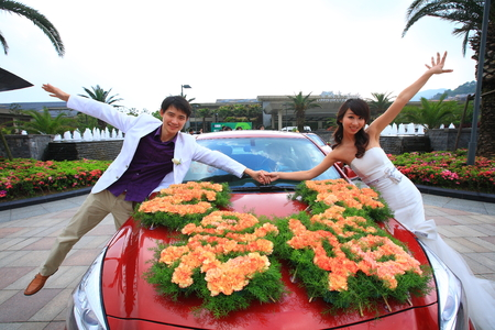 front raise: Wedding couple posing with the bridal car