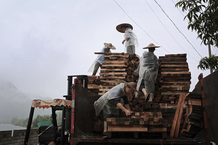 enhancement: Workers loading wood scaffolds onto the truck in the rain