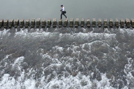 fourties: A man crossing the river on stone walkway