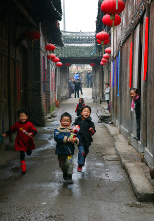 45 years old: Children running along the traditional Chinese streets Editorial