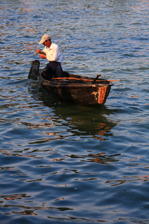 lowering: Fisherman lowering wire fish basket into the water