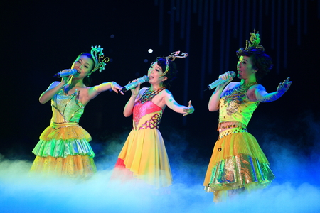 only three people: Women singing on stage