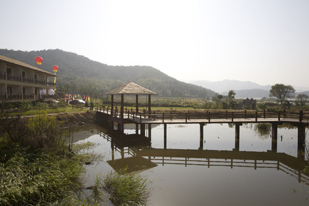 accommodation: Wooden bridge on the lake leading to a village accommodation