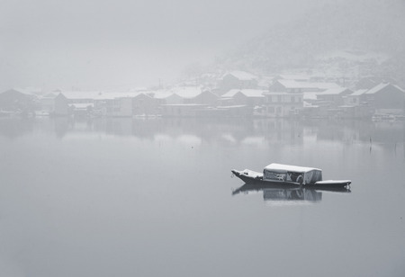 capped: A snow capped boat in a lake