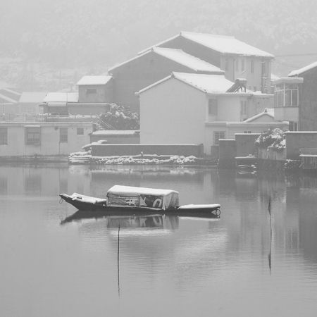 snow capped: A snow capped boat in a lake