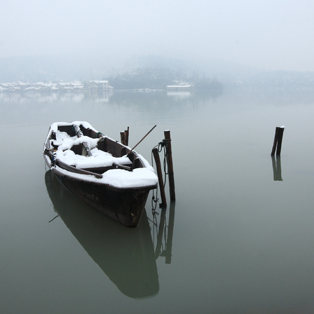 capped: A snow capped boat on the lake