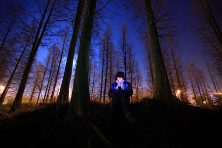 torchlight: Man holding a torchlight to his face in the forest Editorial