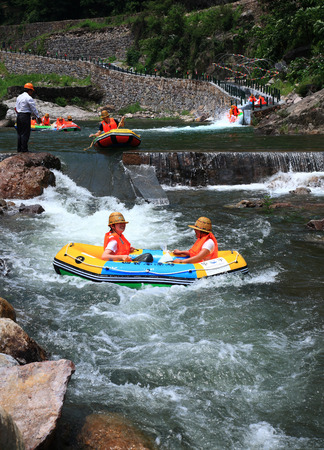 obscured face: People enjoy rafting in stream