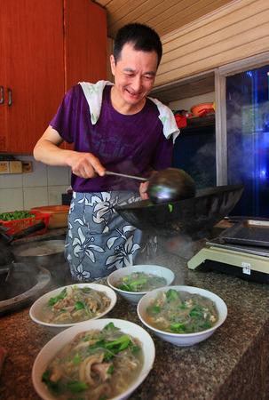 hawker: A hawker serving beef noodles