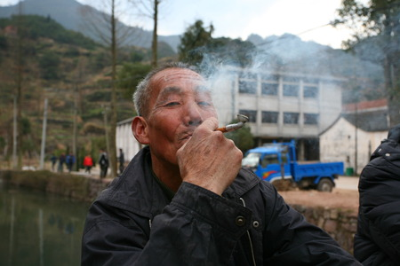 only two people: Old man smoking