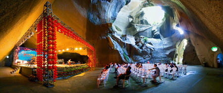 attending: People attending a performance in a cave Editorial