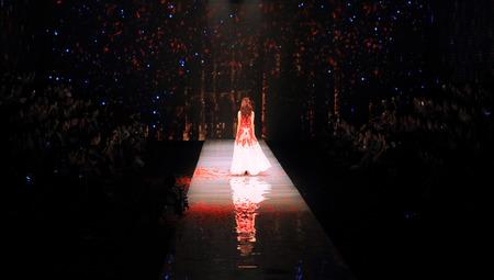 strutting: A model walking back in a fashion runway Editorial