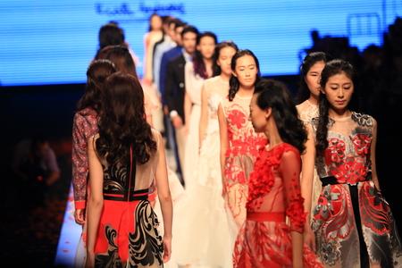 strutting: Models walking down the fashion runway
