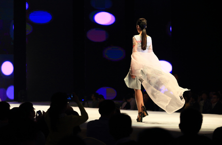 runway fashion: A model walking down the fashion runway Editorial