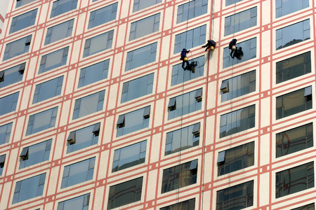 risky job: Three workers cleaning windows Editorial