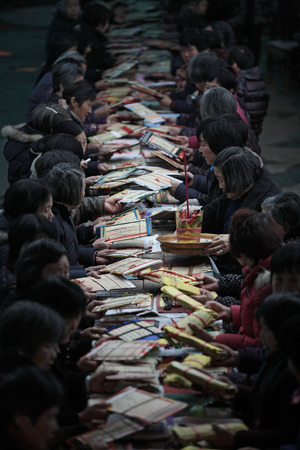 joss: Long table of people passing joss paper packets