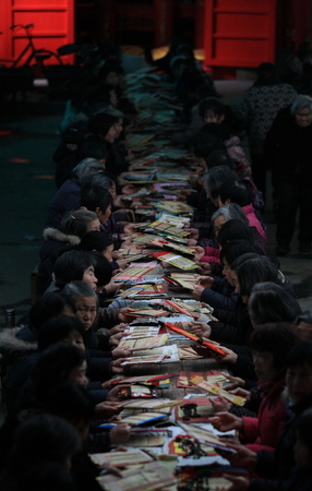 only senior women: Long table of people passing joss paper packets