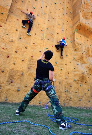 recreational climbing: People climbing a rock climbing wall Editorial