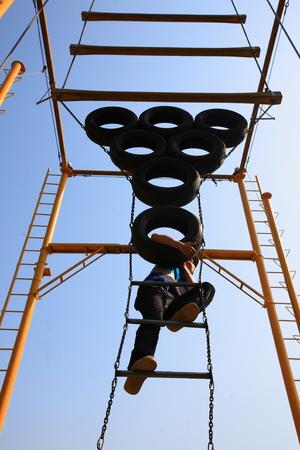 recreational climbing: Man climbing up some tyres