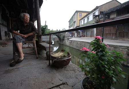 80 plus years: An old lady sitting beside a canal Editorial