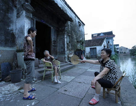 three people only: People chatting by a canal