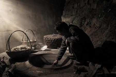 en cuclillas: Una persona que se pone en cuclillas en la antigua cocina