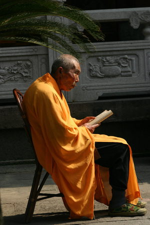 sutra: A monk sitting with sutra in his hands