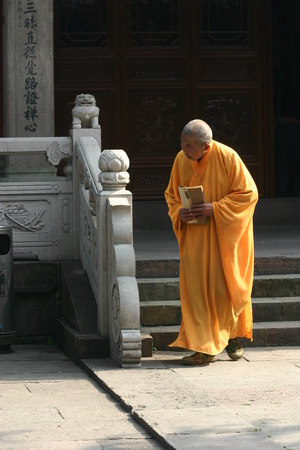 sutra: A monk walking with sutra in his hands Editorial