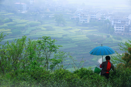 villager: A villager holding an umbrella on the hill
