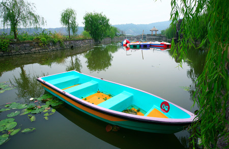 full willow: Neon colored boats in pond Editorial