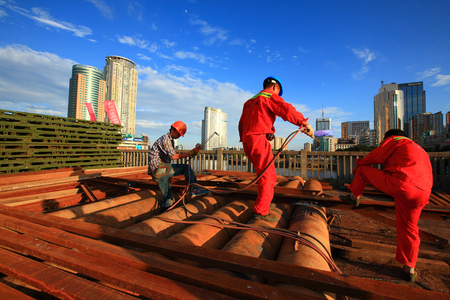 three people only: Construction workers welding in the city Editorial