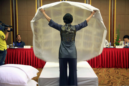 contestant: A contestant folding bed sheets