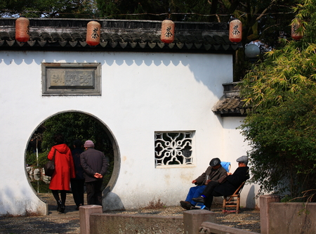 moon gate: View of people at a wall with moon gate