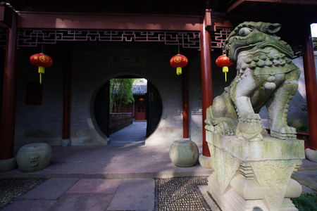 moon gate: View of a Chinese guardian lion infront a moon gate
