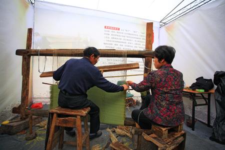 loom: Senior man and woman weaving straw mat with weaving loom