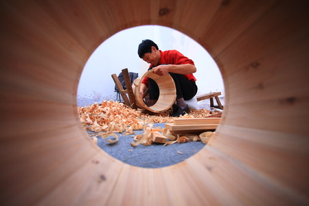 crafting: View of a craftsman crafting a wooden bucket through another unfinished bucket Editorial