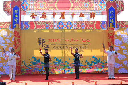 performers: Four performers on stage during the temple festival