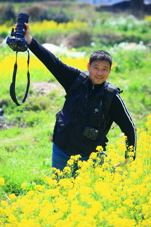 high up: Man holding a camera high up in a flower field Editorial