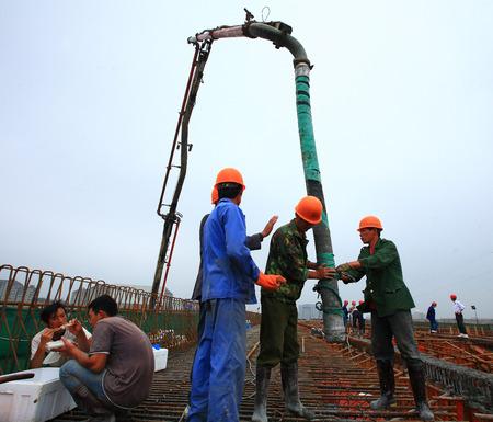 concrete pump: Construction workers working with a concrete pump
