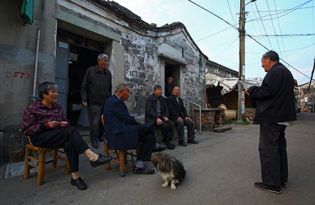 only senior men: A group of elderlies chatting outside a house