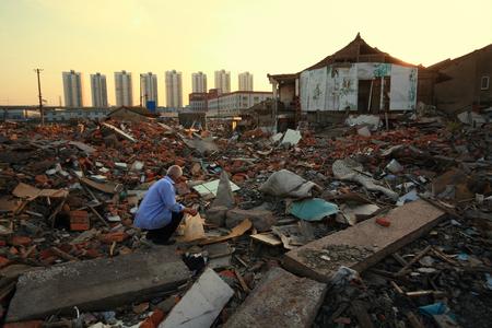 en cuclillas: Un anciano se pone en cuclillas en un montón de escombros
