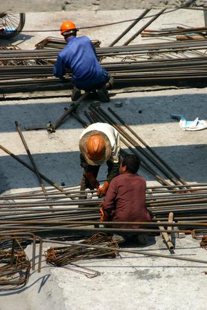collared shirt: Construction worker arranging steel bars