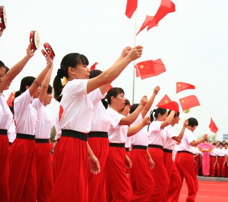 raise the white flag: Women waving china flags and tambourine Editorial