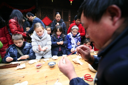 villager: Villager teaching children to mould the rice cakes