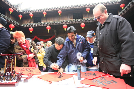 experiencing: Tourists experiencing Chinese calligraphy