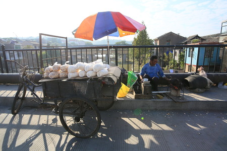 one mature man only: Man selling food on the roadside
