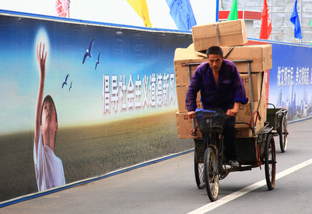 tricycle: View of a man riding a loaded cargo tricycle Editorial