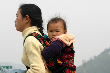 parentage: Woman carrying a baby on her back Editorial