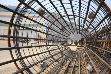 reinforcing: Steel reinforcing bar and workers at a shipyard